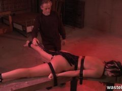Bearded master ties her down face down with leather straps